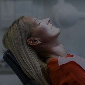 Woman with eyese closed relaxing in dental chair