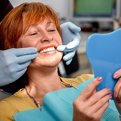 Woman smiling at reflection during dentist appointment