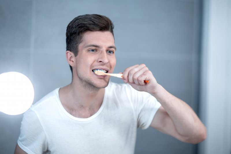 a young man brushing his teeth using a manual toothbrush while standing in front of the mirror