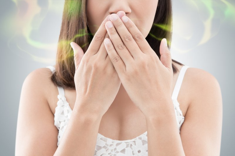 Woman covering her mouth due to bad breath