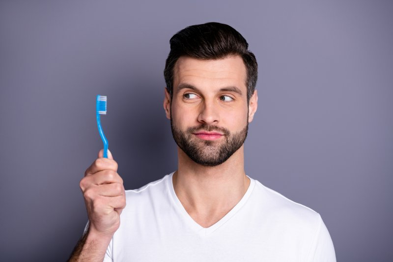 Man looking at toothbrush in his hand