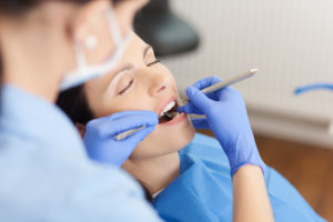 Woman with eyes closed during dental checkup and cleaning